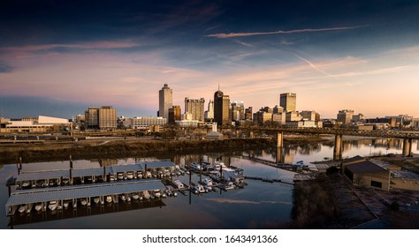 Memphis, Tennessee / USA - Feb 8, 2020: Skyline of downtown Memphis near sunset. Cityscape with skyscrapers, striking contrast, vibrant colors, modern art photography. Reflection in Wolf River Canal.