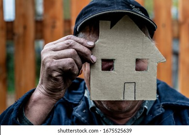 Men 60 years old. He is holding a house cut out of cardboard.