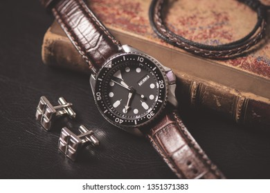 Men accessories on black leather. Closeup at luxury men watch with black dial and leather strap.