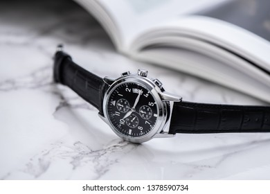 Men accessories on white marble background. Closeup at luxury men watch with black dial and leather strap.