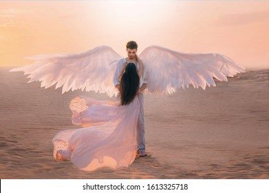 Men angel hugs young woman. Long dark hair dress silk fabric flying flutter wind. costume white wings. Bright color peach pink yellow sunset desert sky. Shoot back rear view turned away without face