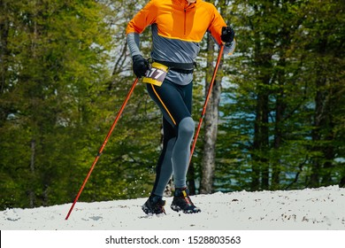 men athlete with trekking poles uphill on snowy trail skyrunning competition