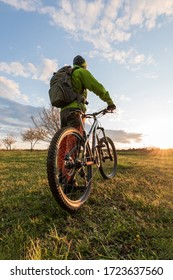 Men with backpack on mountain bike. Bicycle wheels close up image on sunset. Low angle view of cyclist riding mountain bike.