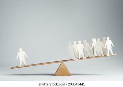 Men balanced on seesaw over a single man
