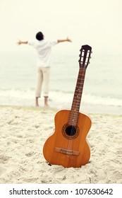 Men at the beach and guitar.