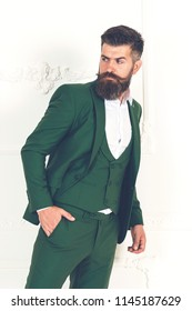 Men with beard clothing, boutiques. Tailor, tailoring. Stylish men's suit. Handsome brutal man suit, tailor in his workshop. Handsome bearded fashion man in classical green costume suit.Amazing style