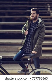 Men with beard is smiling and holding his green jacket and standing near his bike.