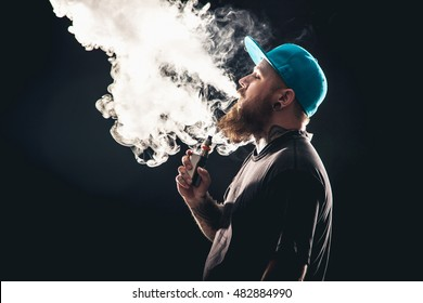Men with beard  in sunglasses vaping and releases a cloud of vapor.