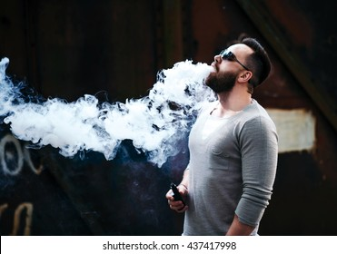 Men with beard vaping outdoor in sunglasses