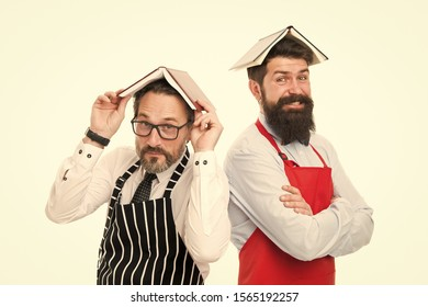 Men bearded apron reading book about culinary. Men in charge household. Some problems. Household duties. Book as roof on head. Household is boring. Who rules in house. Responsibilities of household.