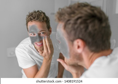 Men beauty caucasian young man applying mud clay detox mask to face. Facial treatment with charcoal for male skin care.