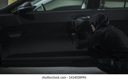 Men in Black Hood Stealing Modern Vehicle. Car Theft Concept Photo.