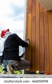 Men build siding Fiber Cement Board on wall exterior