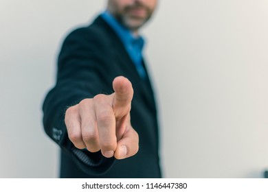 men in business suit pointing in front of camera, light background