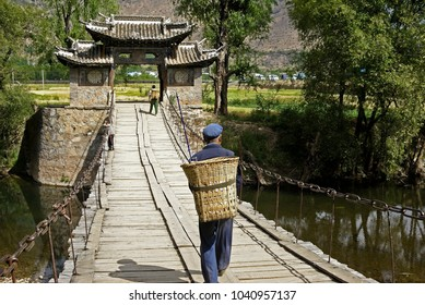 Men carrying baskets on their backs cross a stream on an old wood and chain bridge with a tile-roofed gate at the end, Shigu, Yunnan Province, China
