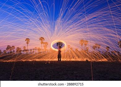 Men cast field Fire steelwool  in the sunrise time.