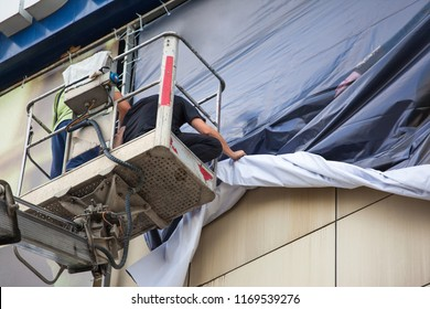 men change an advertising poster on the street standing on the tower of the crane