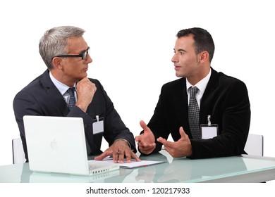 Men chatting at a desk