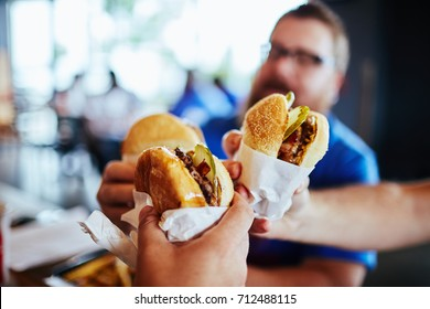 men cheersing with burgers