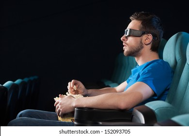 Men at cinema. Side view of excited young men in glasses watching movie at the cinema and eating popcorn