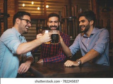 Men are clinking glasses with beer at the pub.