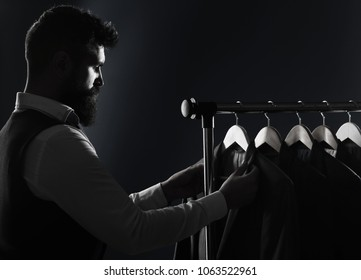 Men clothing, boutiques. Tailor, tailoring. Stylish men's suit. Man suit, tailor in his workshop. Handsome bearded fashion man in classical costume suit. Male suits hanging in a row. Black and white