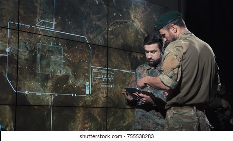 Men in control center calculating coordinates of place of strike to launch nuclear bomb.