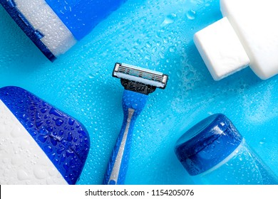 Men cosmetic products, personal hygiene and male hair care and shaving concept with kit of masculine shampoo, aftershave, body wash, gel and razor soaked in water droplets on wet light blue background
