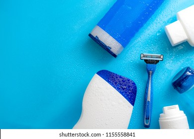 Men cosmetic products, personal hygiene and male shaving concept with masculine shampoo, aftershave, body wash, gel and razor soaked in water droplets on wet light blue background with copy space