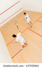 Men at the court playing a match of squash