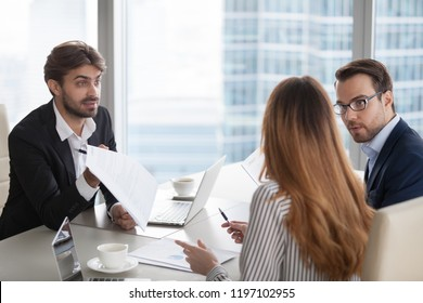 Men criticizing report result of female subordinate. Boss pointing out mistake in document. Workers looking at colleague with disapproval, gender discrimination, dispute concept