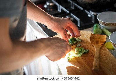 Men cut and cook  cucumbers to make a salad in the kitchen