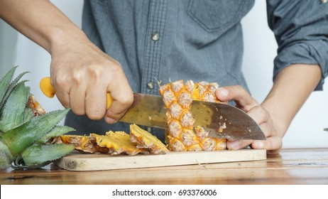 Men are cutting pineapple