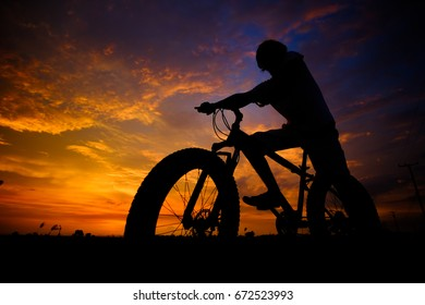 Men cyclistson the sunset background Photographed with backlight technique. light Twilight. fat bike.