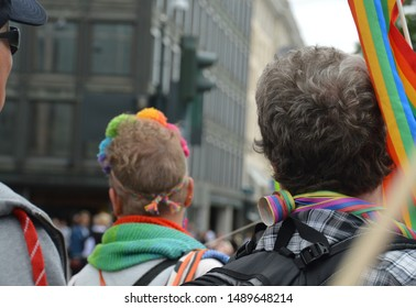 Men of different ages marching at Helsinki Pride parade in 2019, wearing rainbow accessories. Selective focus in the man in front. Standing for equal rights, diversity and inclusion.
