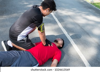 Men are doing first aid by Cardiopulmonary Resuscitation or CPR to friends with sudden cardiac arrest. During exercise together Within the park