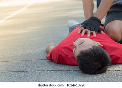 Men are doing first aid by Cardiopulmonary Resuscitation or CPR to friends with sudden cardiac arrest. During exercise together. Within the park