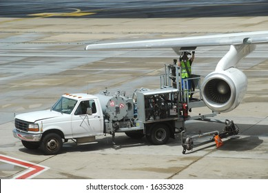 Men doing the JET-A1 fill up of an airplane under the wing on the airport  tarmac