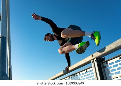 Men doing morning workout outdoors, sportsmen jumping over the fence.