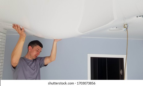 Men is drain water from a stretch ceiling filled with water through a tube. Flood, water leakage from the ceiling in the apartment.