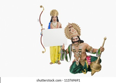 Men dressed-up as Rama and Ravana and holding a blank placard