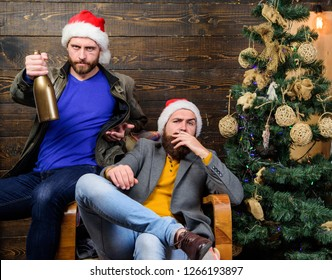 Men drink champagne and smoking. Brutal men celebrate new year near christmas tree. New years resolution. Bad habits to kick before the end of year. Get rid of harmful habits. How to break bad habits.