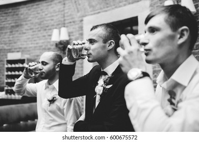 Men drink whisky standing in the row