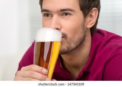 Men drinking beer. Portrait of handsome young men drinking beer and looking away