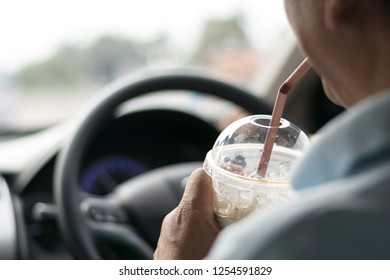 men drinking cup of cold coffee while driving a car.Dangerous driving concept
