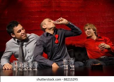 Men drinking shots in night club