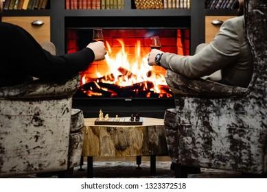 men drinking wine near fireplace