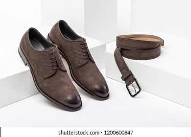 Men elegant brown leather shoes and belt on a white box