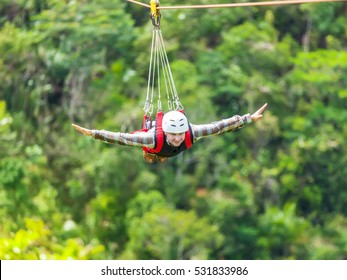 Men enjoying zip-line flying over the forest