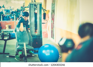 Men exercise gym fitness concept, Asian man playing weight traning by dumbbell for good health of body in gym  and workout in fitness club center